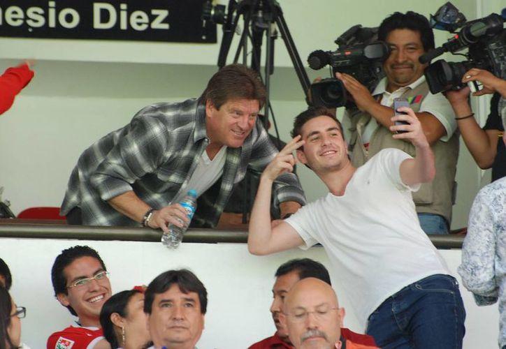 Miguel Herrera, con quien un aficionado del Toluca se toma una 'selfie', estuvo presente en el partido ante León, en busca de un lateral derecho para el Tri. (Notimex)