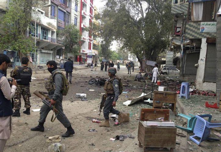 Miembros de las fuerzas de seguridad inspeccionan el lugar de un atentado suicida cerca de un nuevo Banco de Kabul en Jalalabad, al este de Kabul, Afganistán. (Agencias)