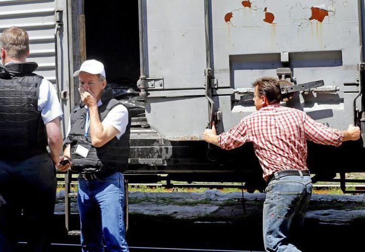 Inspectores internacionales revisan ante uno de los vagones refrigerados en los que se almacenan los restos de las pasajeros del avión. (EFE)