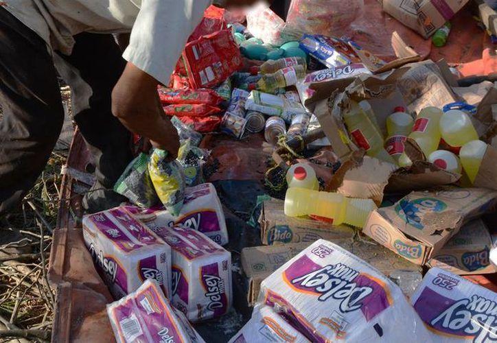 Algunas  personas que 'llegaron' hasta el lugar donde se volcó un tráiler cargado de abarrotes, se llevaron parte de las mercancías. (Victoria González/SIPSE)