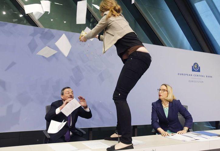 Una mujer que protestaba contra la política del Banco Central Europeo se subió sobre el escritorio del presidente de la entidad, Mario Draghi, mientras éste ofrecía una conferencia de prensa. (AP)