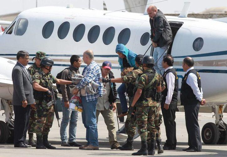 Un grupo de la banda internacional de narcotraficantes, es escoltado por policías peruanos a su llegada a la base de la Policía Aérea, ayer en Lima. (EFE)