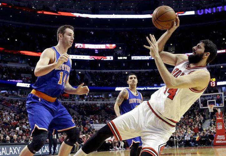 Nikola Mirotic (44), de Bulls, lanza a la canasta frente a Jason Smith (14), de Knicks, en la segunda mitad del partido de temporada regular de la NBA en Chicago. (Foto: AP)