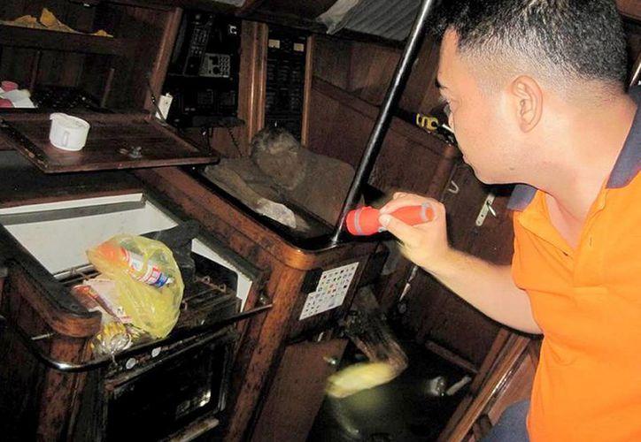 Foto proporcionada por la Oficina de Información Pública de Filipinas de la Guardia Costera en Manila, donde se ve a un funcionario de la guardia costera inspeccionar los restos de un hombre en un yate. (Agencias)