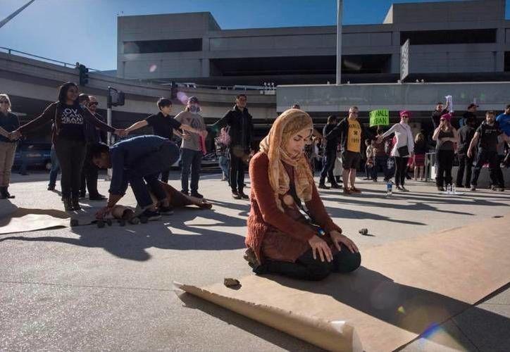 Fotografía de una mulsulmana protestando en el Aeropuerto Internacional de Los Angeles. 'El Chivo' coloco en el pie de foto 'No muro. No prohibiciones.' (Instagram/ chivexp)