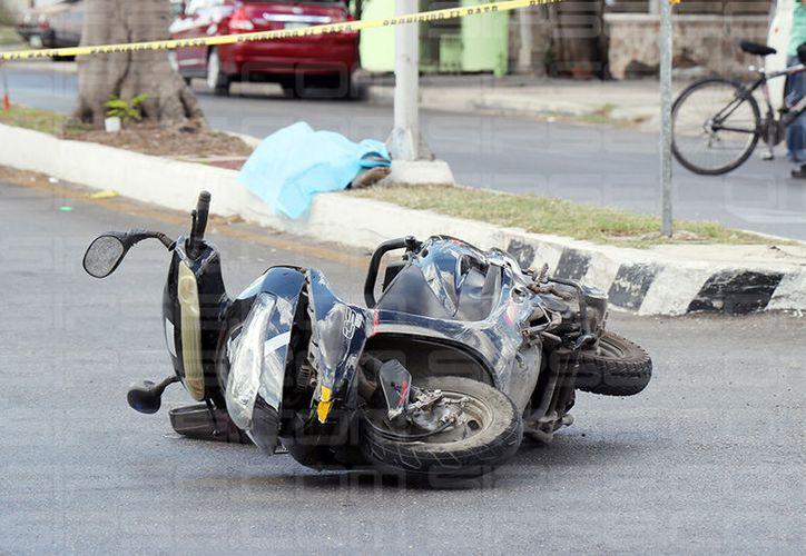 La imagen muestra la motoneta tirada a media calle y el cuerpo del motociclista, al fondo, junto al poste. (Milenio Novedades)