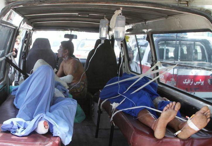 Hombres afganos heridos en una ambulancia tras un accidente en la carretera principal que conecta la capital, Kabul, con la ciudad sureña de Kandahar, en la provincia de Ghazni, al este de Kabul, en Afganistán, el domingo 8 de mayo de 2016. (AP Foto/Rahmatullah Nikzad)