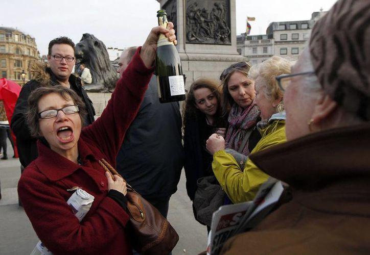 """Varias personas bebían cervezas en lata y botellas de vino coreando: """"¡Está muerta!"""". (Agencias)"""