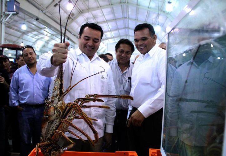 La muestra inaugurada ayer incluye productos marinos, como la langosta que levanta el alcalde, Renán Barrera, frente al gobernador, Rolando Zapata. (José Acosta/SIPSE)