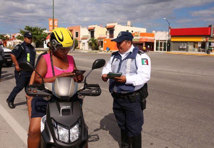 Elementos policíacos reparten trípticos con una serie de recomendaciones. (Adrián Barreto/SIPSE)