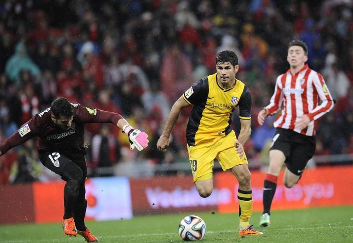 Diego Costa (c) esquiva al portero rival Herrerin y anota el tercer gol del Atlético de Madrid en el juego de vuelta de cuartos de final de Copa del Rey contra el Bilbao. (Agencias)