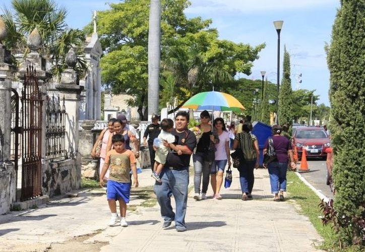 Los cementerios se llenaron hoy de colores gracias a las multitudinarias visitas de los deudos. (Theany Ruz/SIPSE)