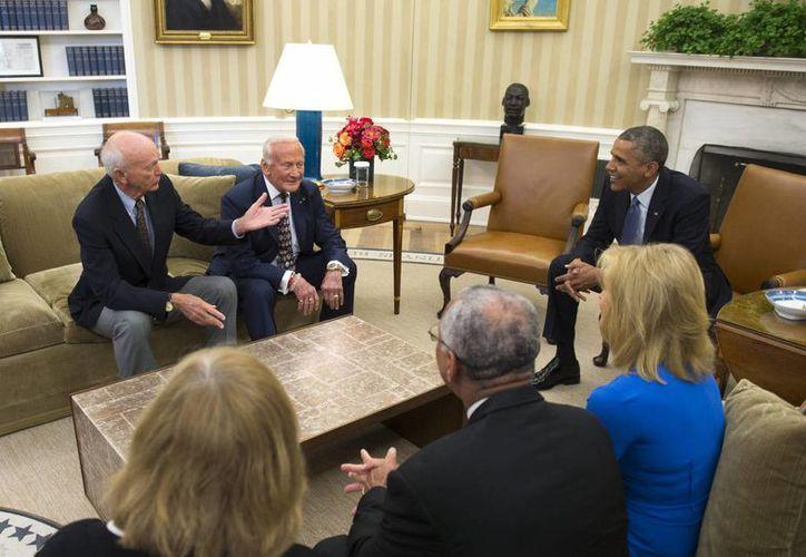 El presidente Barack Obama (d) conversa con Michael Collins y Buzz Aldrin, astronautas del Apollo 11, en el despacho Oval de la Casa Blanca, en Washington, EU, el 22 de julio del 2014. (EFE)