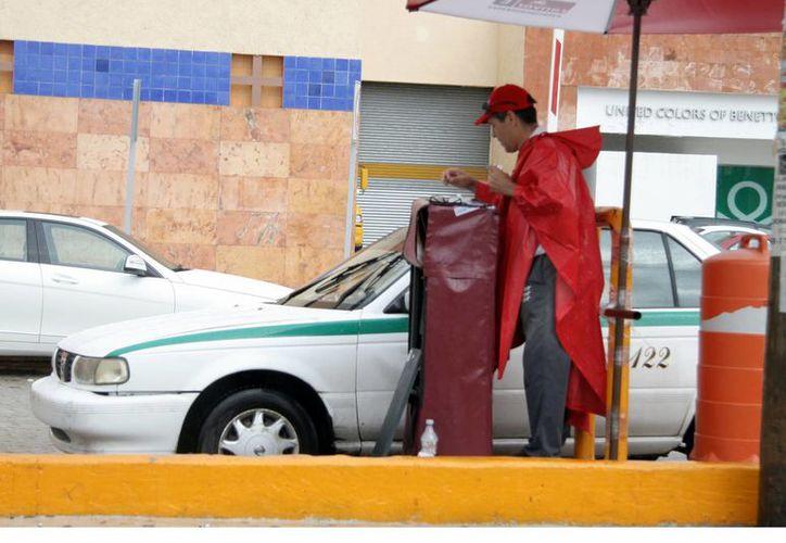 Personal de la plaza realiza el cobro manual. (Luis Soto/SIPSE)