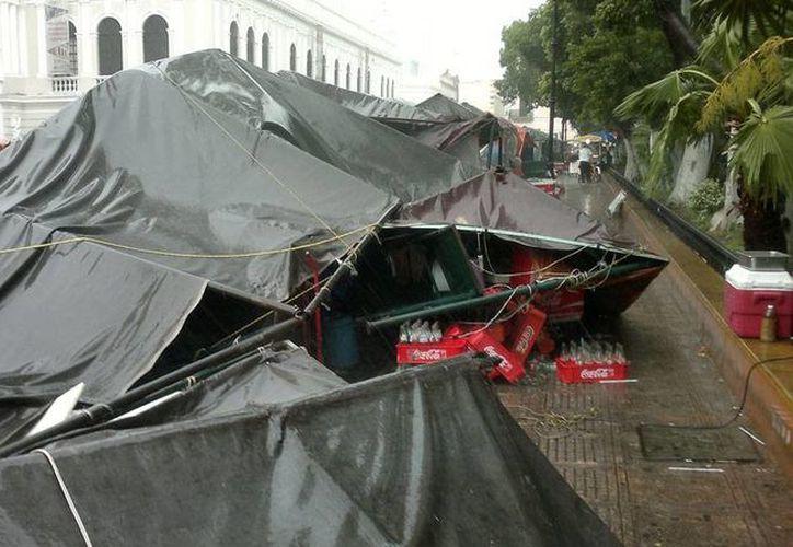 La lluvia que cayó ayer sobre todo en el Centro de Mérida causó que los toldos de los puestos de Mérida en Domingo cayeran. No hubo heridos y los daños materiales fueron menores. (Milenio Novedades)