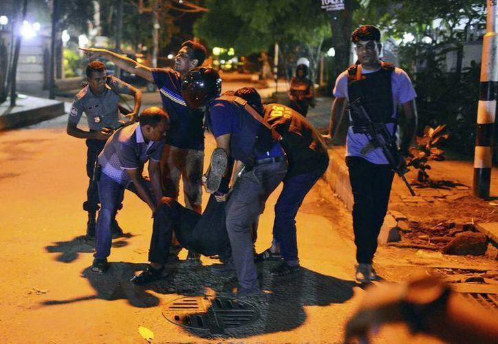 Un grupo de personas ayuda a uno de los heridos durante la toma de rehenes en un restaurante de Daca, la capital de Bangladesh. (AP)
