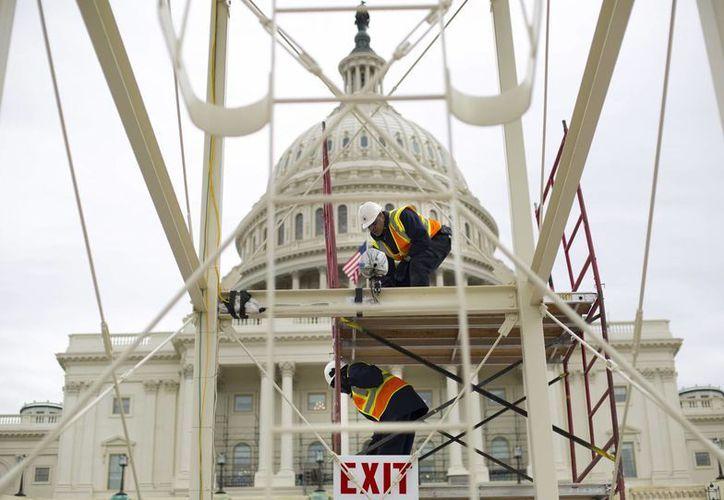 Trabajadores instalando la tribuna para la ceremonia de investidura de Donald Trump en la escalinata del Capitolio en Washington. (AP/Pablo Martinez Monsivais)