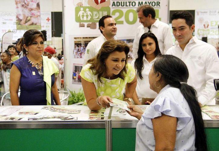 La presidenta del DIF estatal, Sarita Blancarte de Zapata entrega un volante a una mujer de la tercera edad en la Expo adulto mayor. (Milenio Novedades)