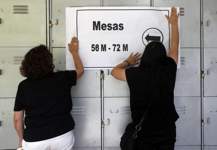 Dos mujeres pegan un cartel informativo en uno de los colegios de votación de la segunda vuelta de las elecciones presidenciales, en Santiago de Chile. (EFE)