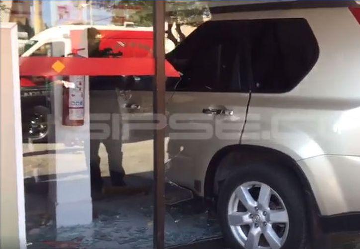 Más de medio vehículo terminó en el fondo del comercio. (Captura de pantalla de SIPSE Noticias)