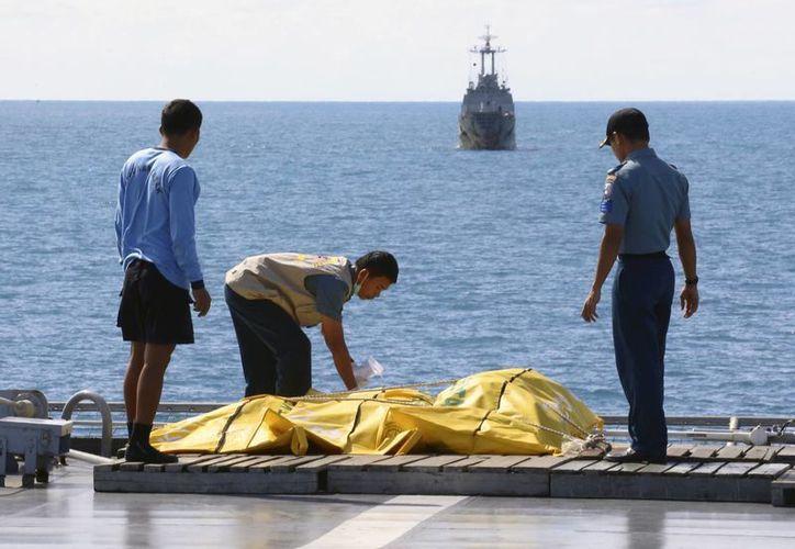 Los rescatistas inspeccioonan la tarea de extracción de cadáveres del accidentado Vuelo 8501 de AirAsia a bordo de una nave indonesia en el Mar de Java. (Agencias)