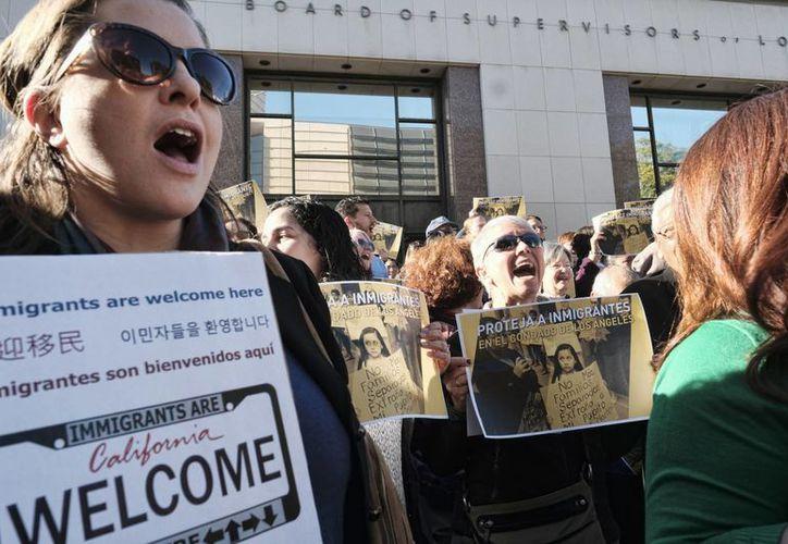 Manifestantes expresan su apoyo a inmigrantes en las escalinatas de la sede de la Junta de Supervisores del Condado de Los Ángeles, el Kenneth Hahn Hall of Administration, en el centro de Los Ángeles, el martes 20 de diciembre del 2016. (AP Foto/Richard Vogel)