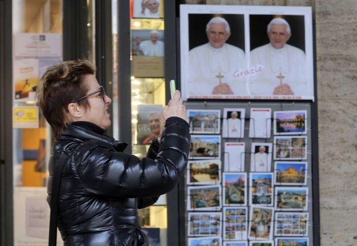 Una mujer toma fotos a un retrato de Benedicto XVI afuera de una librería cercana al Vaticano. (Agencias)
