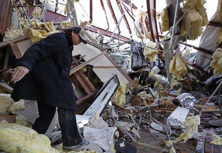Sandra McDaniel camina entre los escombros del edificio de la compañía gasera Jack Morris, en Columbia, Mississippi. (Foto AP/Ro0gelio V. Solís)