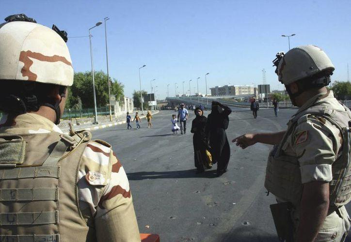 Dos mujeres se aproximan a unos miembros de las fuerzas de seguridad iraquíes en Bagdad, Irak. (Archivo/EFE)
