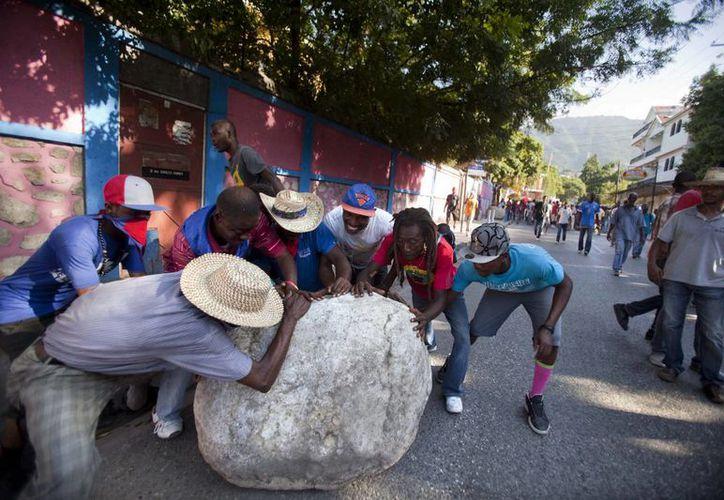 Manifestantes antigubernamentales mueven una gran piedra a la mitad de la calle para obstruir el paso, en Puerto Príncipe, Haití. (Agencias)
