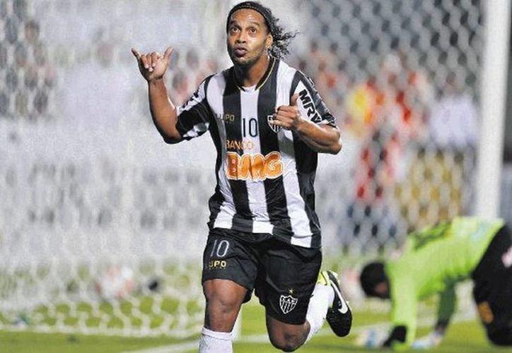 El brasileño Ronaldinho le queda a deber al Querétaro. Se le ve más en fiestas que en el terreno de juego. (AP/Archivo)