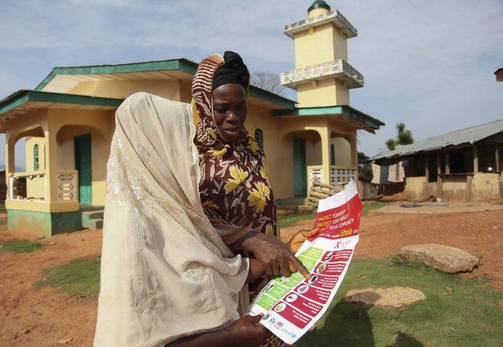 Unas mujeres observan un cartel con consejos para prevenir el ébola, en el distrito de Zorzor en Lofa, Liberia. (Archivo/EFE)
