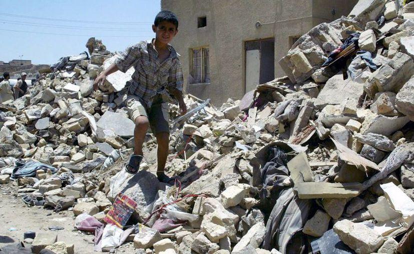 Un niño iraquí camina entre los escombros de su casa después de un ataque aéreo en Diwaniya, al sur de Irak. (Archivo/EFE)