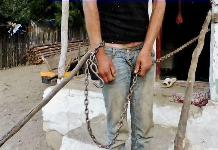 Imagen tomada de un video de la Policía rumana donde se ve a un hombre encadenado afuera de una casa en el pueblo de Berevoiesti, Rumania. (Agencias)