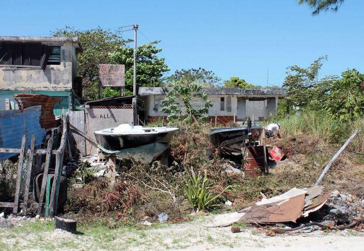 Los propios vecinos se dan a la tarea de limpiar los terrenos, mismos que ofrecen un triste espectáculo a los escasos visitantes. (Ernesto Neveu/SIPSE)