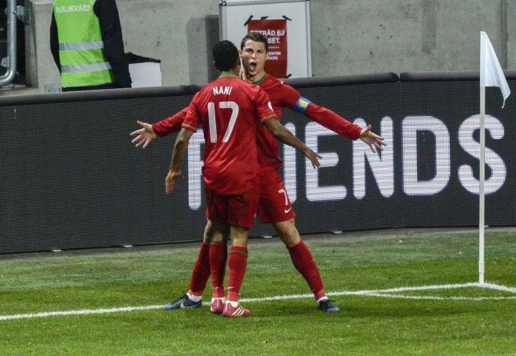 Cristiano Ronaldo (d) celebra con Nani después de anotar un gol ante Suecia en el estadio Friends Arena en Solna, Suecia. (EFE)