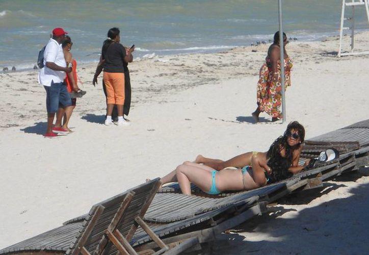 Turistas tomando el sol en la playa de Progreso. (Manuel Pool/SIPSE)