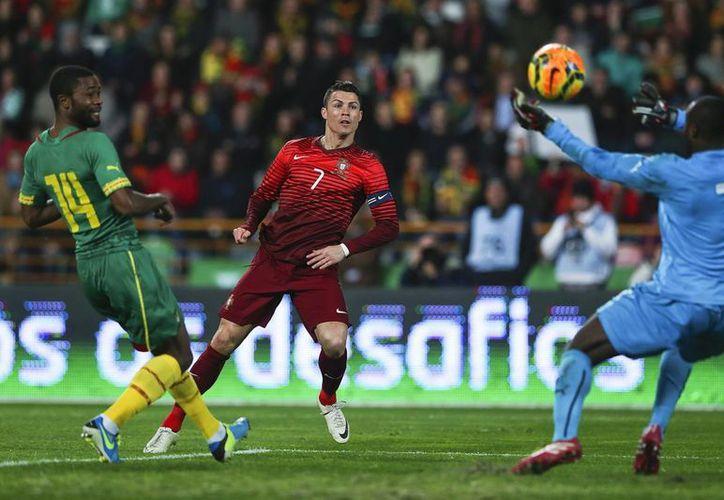 Cristiano Ronaldo (c), disputa el balón con Guy-Roland Ndy Assembe (d), en el partido amistoso entre Portugal y Camerún en el estadio Magalhaes Pessoa en Leiria, Portugal. (EFE)