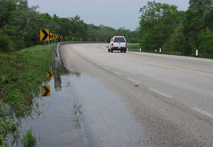Usuarios de la carretera federal  alertaron a las corporaciones policíacas sobre el nivel del agua. (Manuel Salazar/SIPSE)