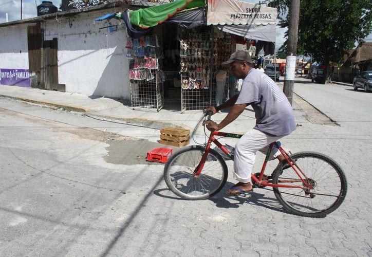 Los pobladores colocan una mezcla de cemento para tapar los baches en las avenidas principales. (Sara Cauich/SIPSE)