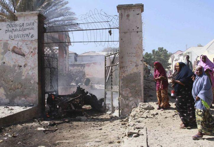 Varias mujeres permanecen junto a los restos de un coche bomba que explotó cerca del Palacio Presidencial en Mogadiscio, Somalia. (EFE/Archivo)