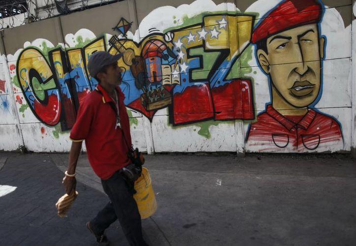 Transeúntes caminan frente a pintadas de apoyo al presidente Hugo Chávez este 14 de enero, en el centro de Caracas (EFE)