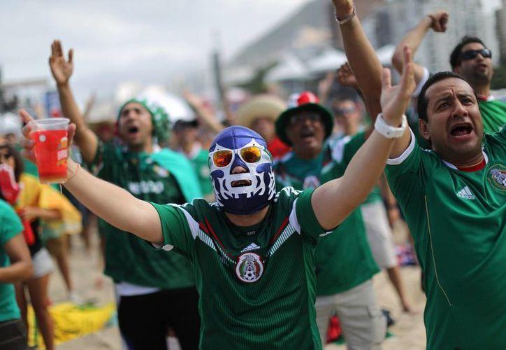 Un aficionado disfrazado con una típica máscara de lucha libre mexicana observa el partido entre México y Camerún en Copacabana. (Foto: AP)