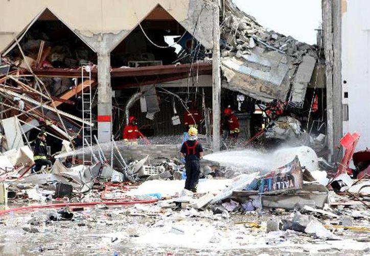 Los bomberos trabajan entre los escombros del restaurante en que explotó un depósito de gas. (AFP)