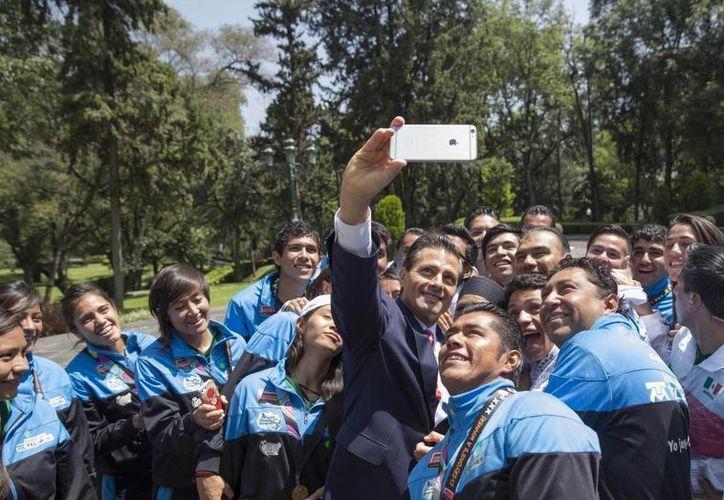 El presidente Enrique Peña Nieto se toma una selfie con las selecciones varonil y femenil de México que obtuvieron sendos títulos en la Homeless World Cup. (presidencia.gob.mx)