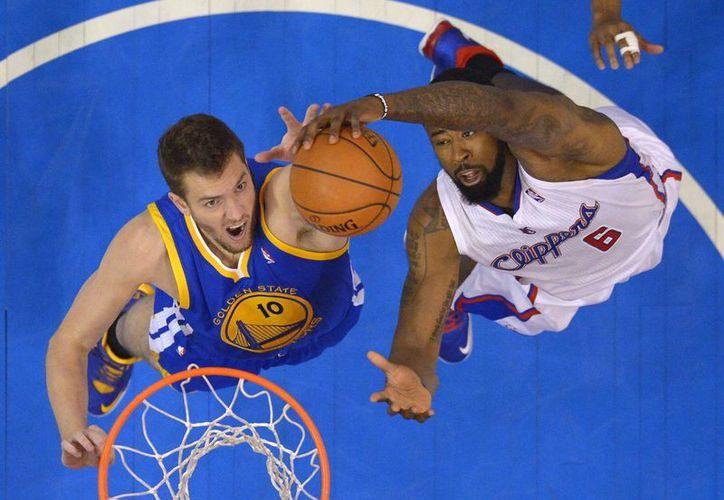 David Lee, de Warriors (i), disputa un rebote con DeAndre Jordan, de Clippers, en el quinto juego que ganó el equipo de Los Angeles. (Foto: AP)
