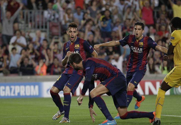 Gerard Piqué (c) rompió el cero en el marcador con una jugada a balón parado al rematar de cabeza un centro de Messi. (Foto: AP)