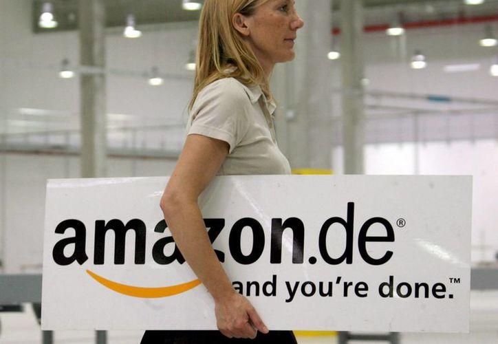 """Una mujer con el logo de la empresa de ventas en internet """"Amazon"""" bajo el brazo pasa por una de las salas de la compañía en Leipzig, Alemania. (Archivo/EFE)"""