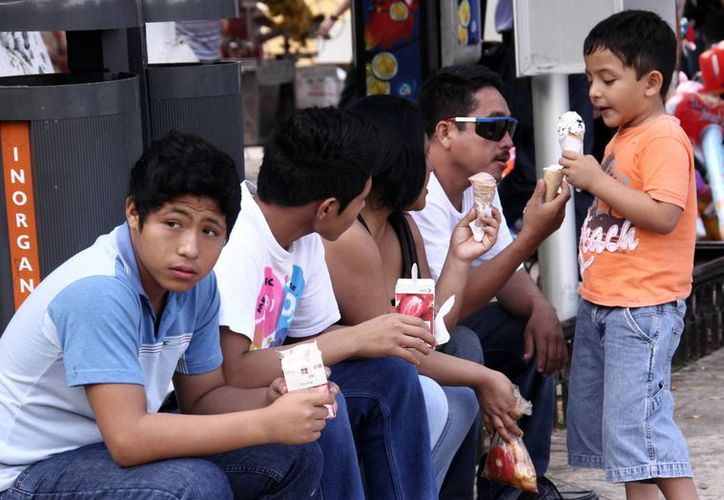 Una familia toma un descanso y se refresca durante un recorrido dominical por la Plaza Grande. (SIPSE)