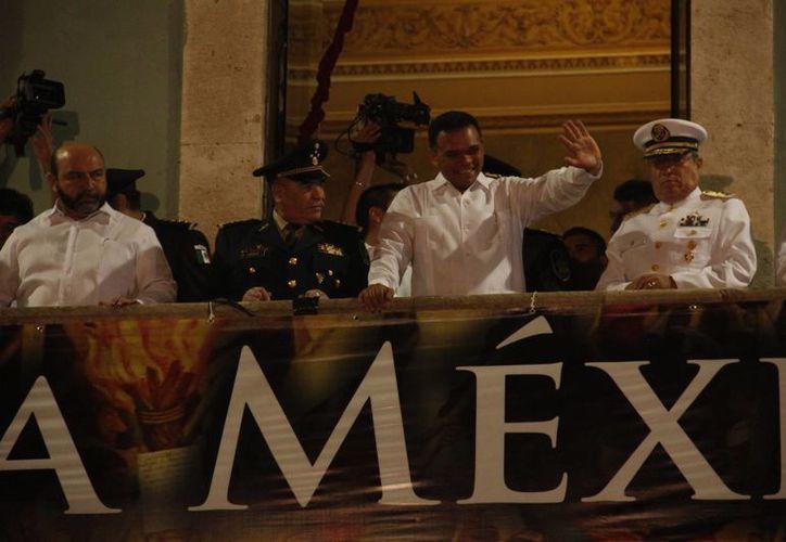El gobernador Rolando Zapata saluda a la gente desde el balcón principal, durante la ceremonia del Grito. (SIPSE)